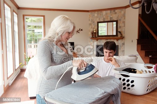 802472024 istock photo Men looging pregnant woman ironing clothes at home 583692844