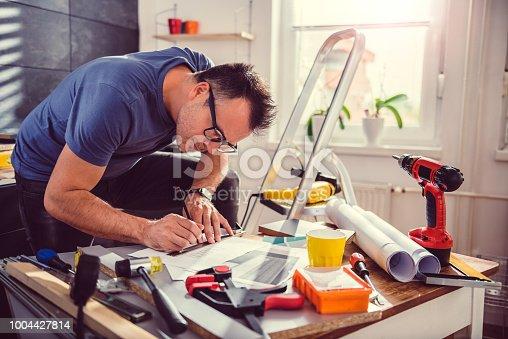 512113530 istock photo Men looking at blueprints during kitchen renovation 1004427814