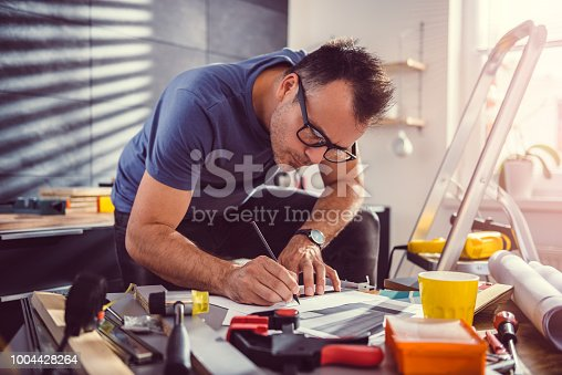 512113530 istock photo Men looking at blueprints during kitchen renovation 1004428264