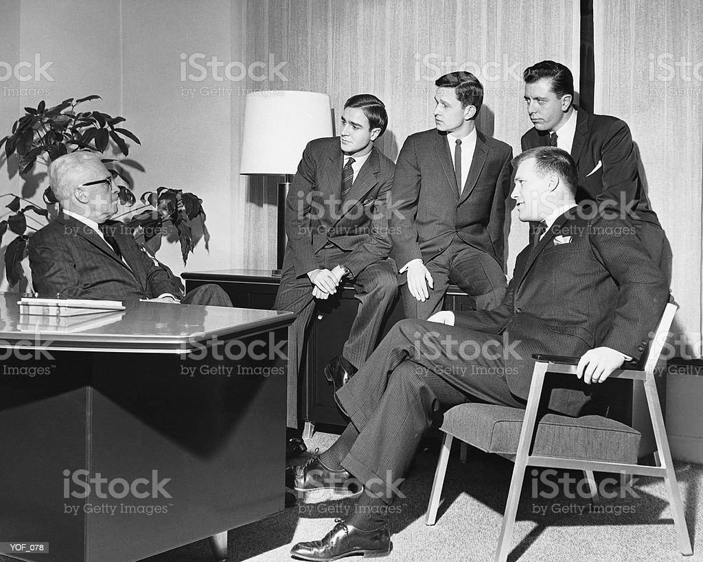 Men looking at group in meeting royalty-free stock photo