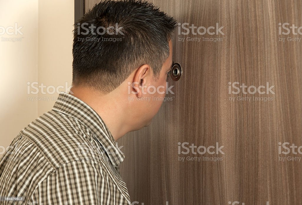 men looking into spy hole stock photo