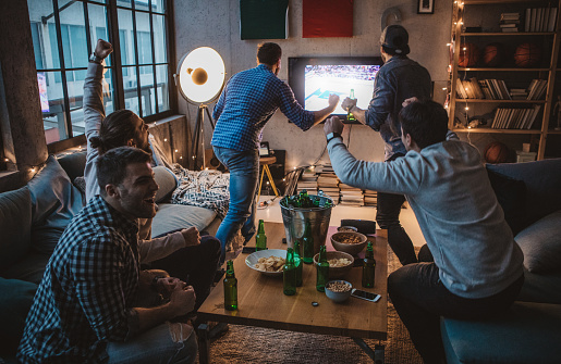 Group of young men gather at home party. They are watching basketball game on tv, drinking beer, making jokes and cheer for their team.