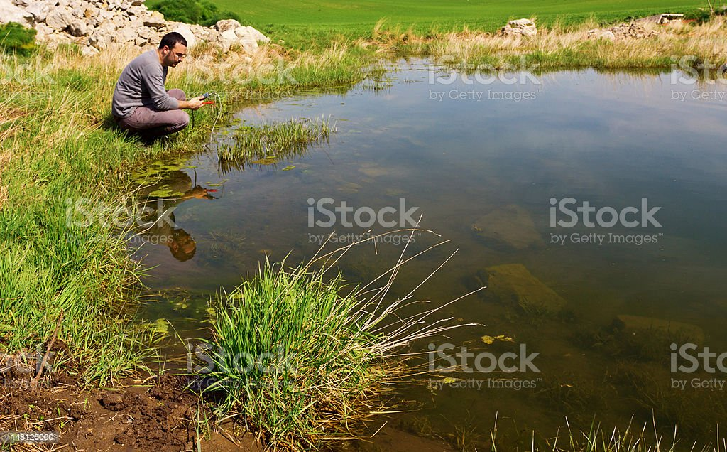 Men measuring water quality of a pond stock photo