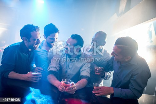 Men night out having fun at a club drinking and looking very happy