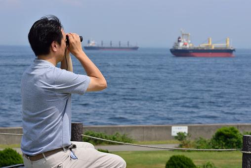 Men of Japan overlooking the sea with binoculars