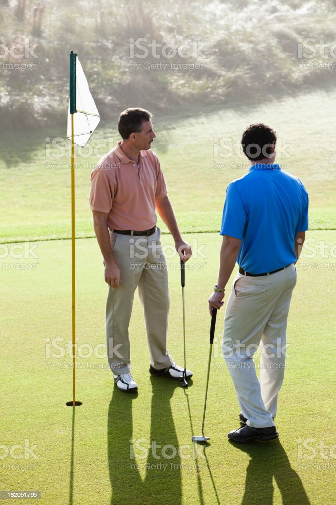 Men on golf course putting green royalty-free stock photo