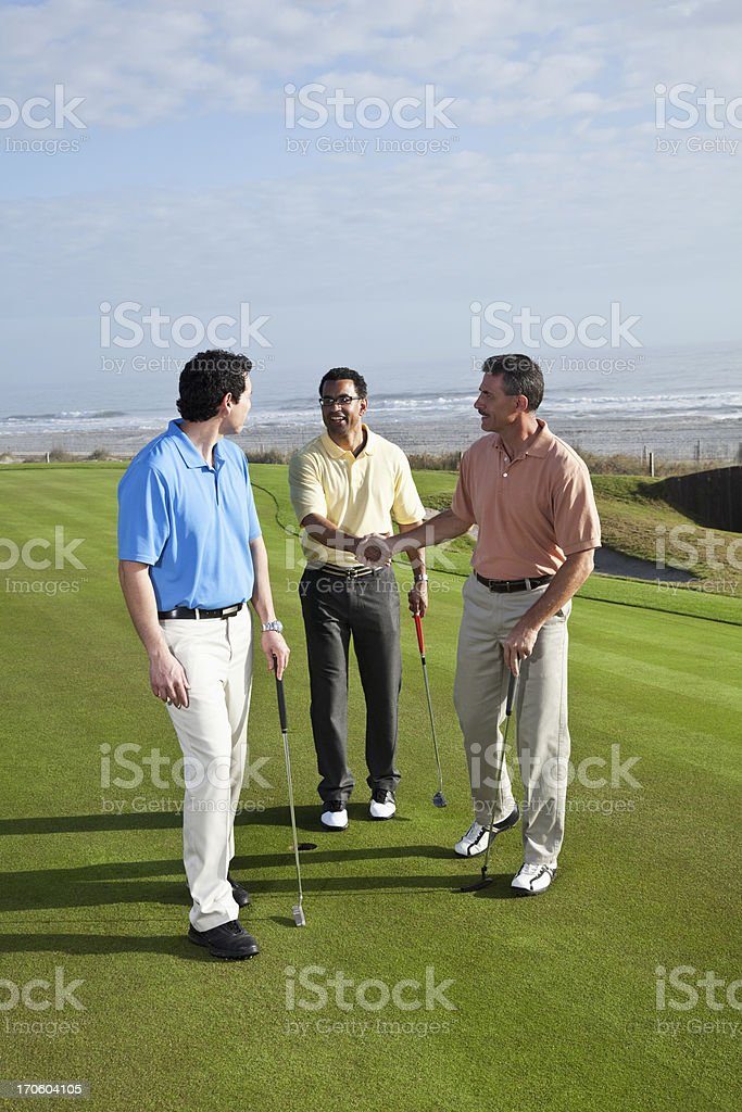 Multi-ethnic men on putting green, shaking hands after finishing...