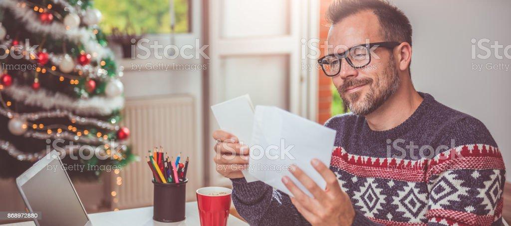 Men opening christmas letter stock photo