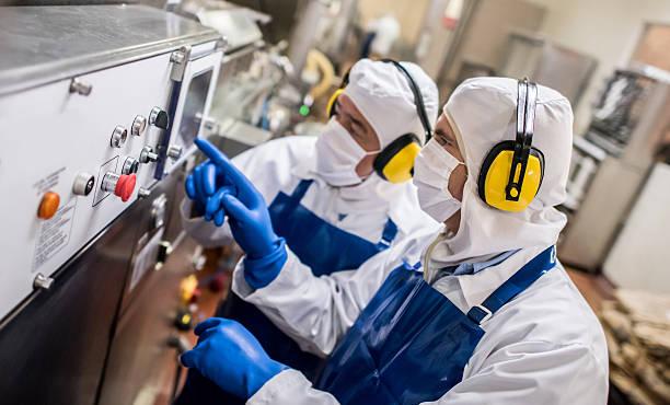 men operating machine at a food factory - nahrungsmittelfabrik stock-fotos und bilder