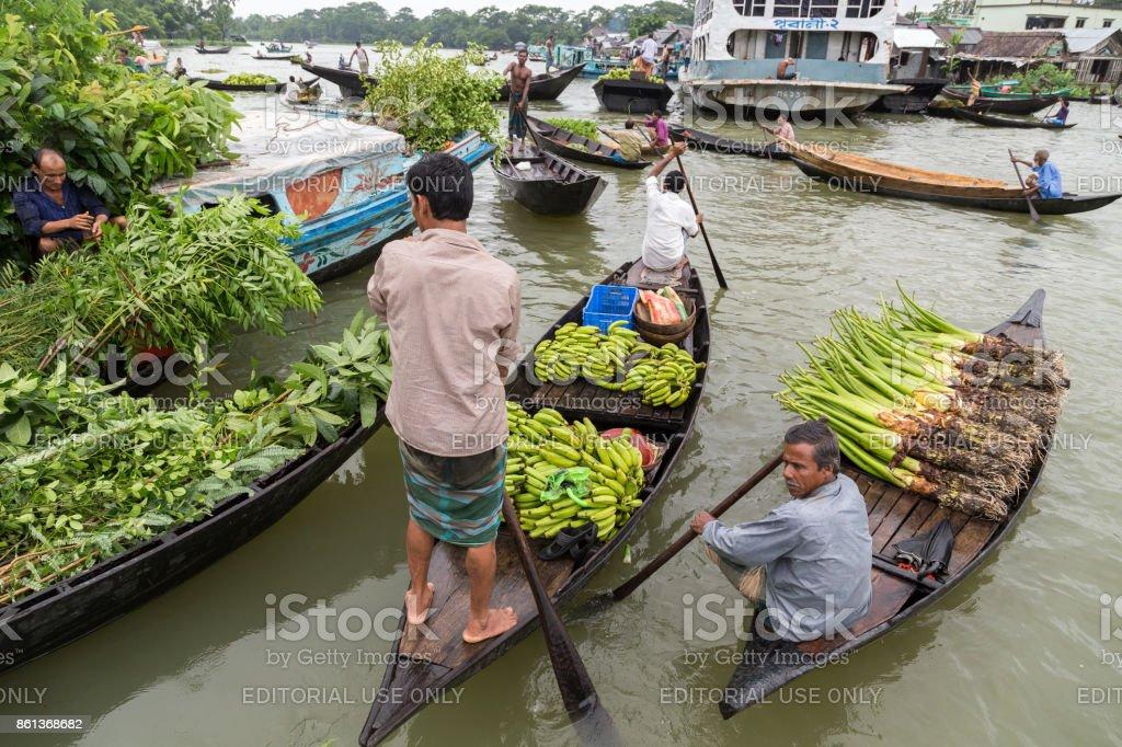 Barisal, Bangladesh - July 12, 2016: Men paddling boats full of bananas and plants at the floating vegetable market stock photo