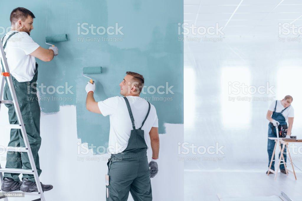 Men painting empty home interior stock photo