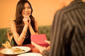レストランで恋人に贈り物を渡す男性
