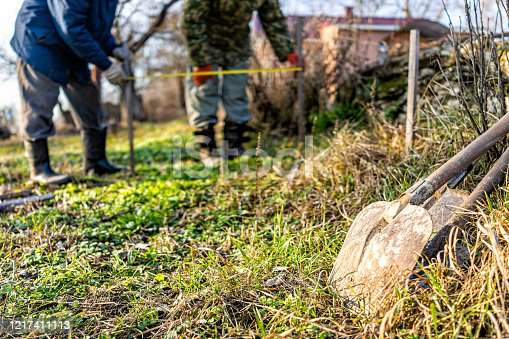 Men people with measuring tape working on vegetable winter garden for post raised bed cold frame in Ukraine dacha and closeup of shovel spade
