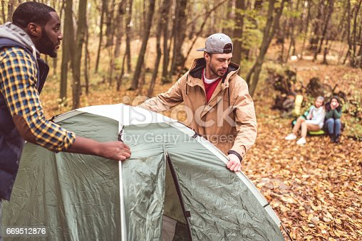 Young men pitching tent in autumn forest with blurred girls sitting on background