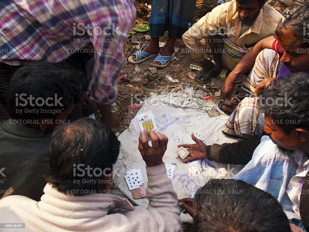 Men play card game on the banks of Buriganga River stock photo