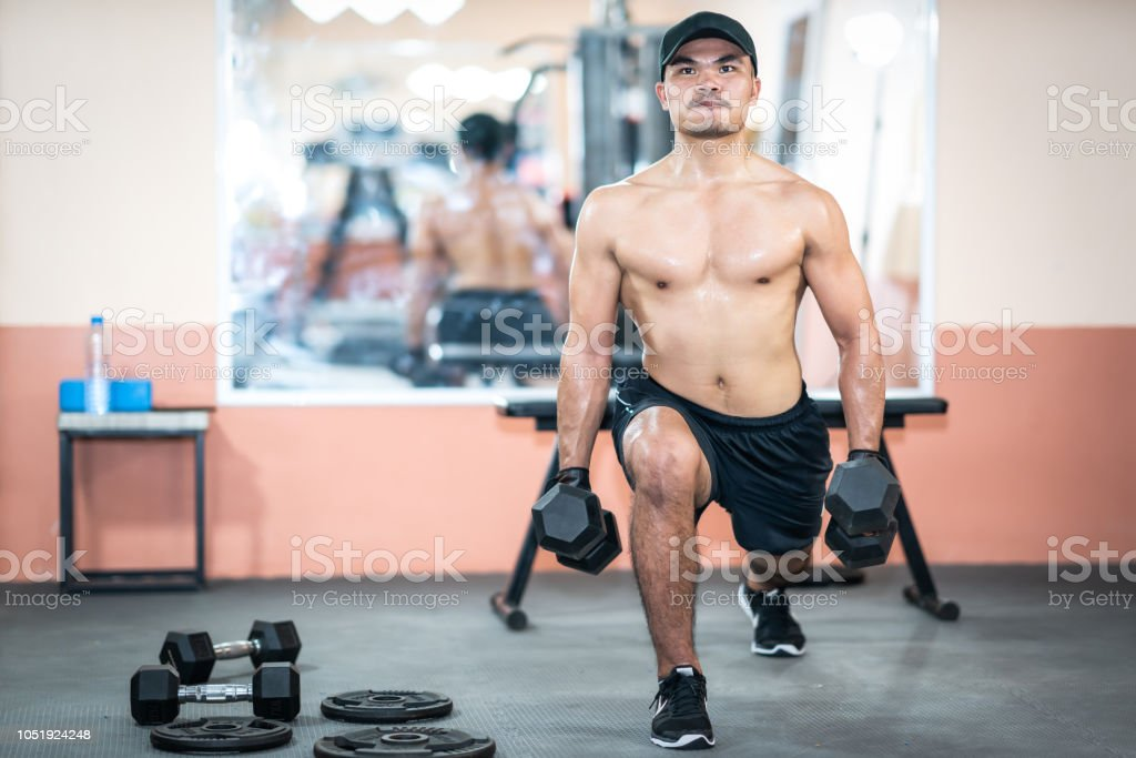 Men Play Exercise Weight Training By Dumbbells In Gym