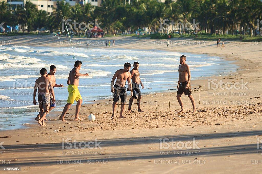 Men play football on the beach stock photo