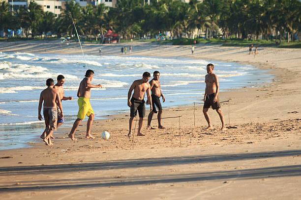 homens jogar futebol na praia - futebol de areia - fotografias e filmes do acervo