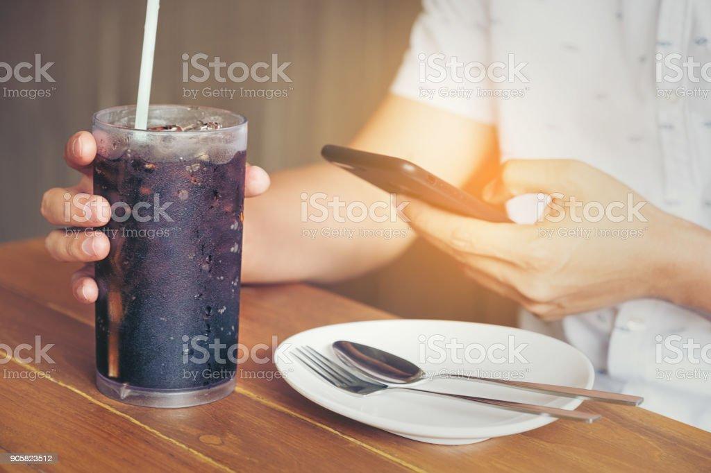 Männer spielen Smartphone und Hand halten Glas weichen Dring in Essen im Café Restaurant warten – Foto
