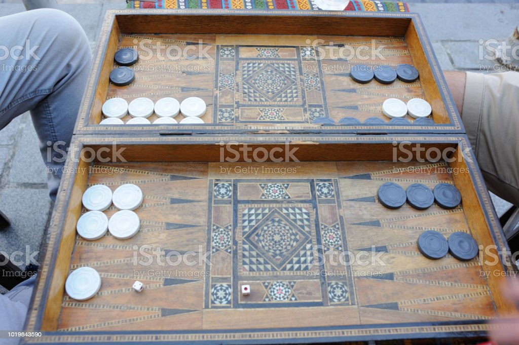 Men playing backgammon board game with an old wooden table, checkers...