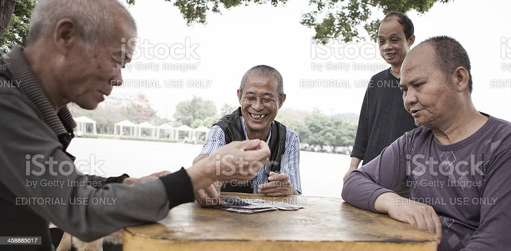 Men playing cards at the park in China stock photo
