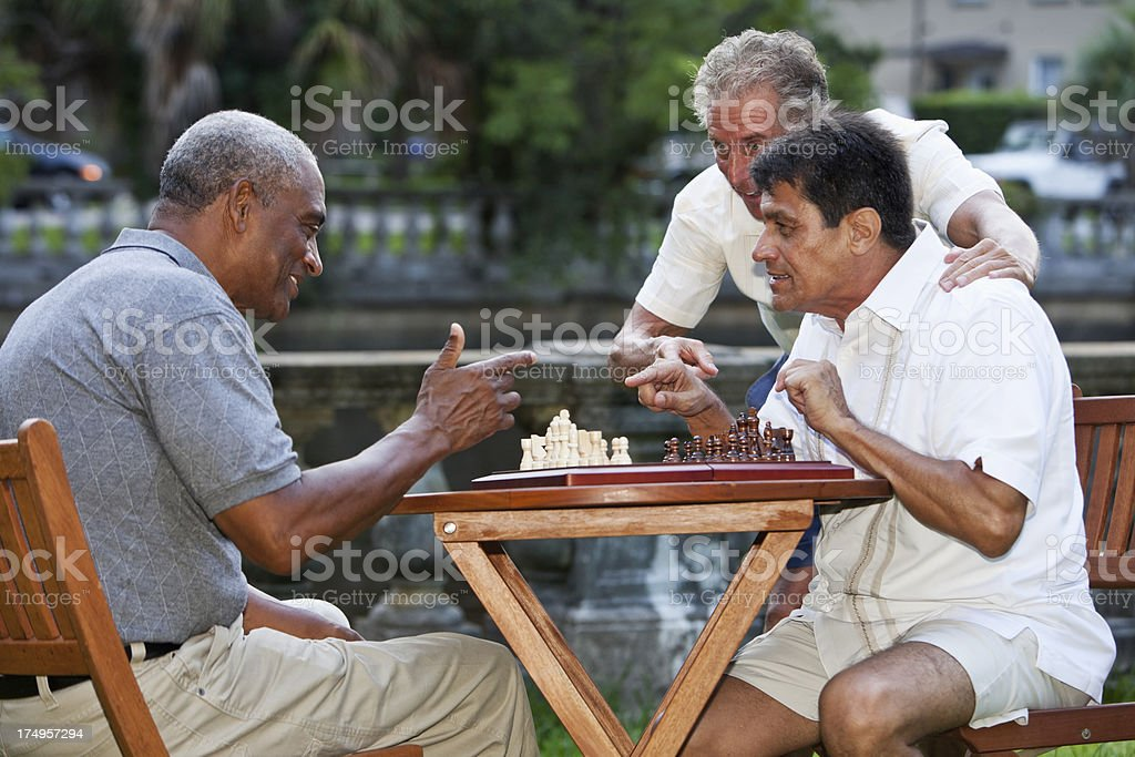 Men playing chess in park stock photo