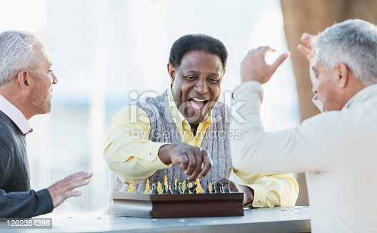 A group of three middle-aged and senior multi-ethnic men in their 50s and 60s playing a game of chess. The view if from over the shoulder of the senior Hispanic man. His African-American opponent is laughing as he reaches for a piece to make the winning move.