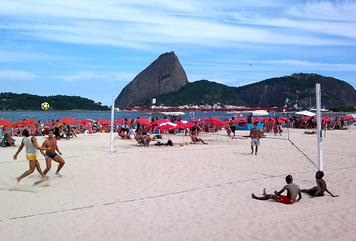 Rio de Janeiro, Brazil - February 20, 2012: Men playing footvolley in Flamengo Beach during a sunny carnival day holiday. In the background: thousands of sunbathers, Guanabara Bay and the Sugarloaf.