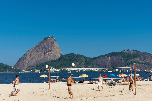 Rio de Janeiro, Brazil - April 7, 2016: Four men play footvolei in Flamengo Beach, in front of the Sugarloaf in a beautiful day. Popular in Rio de Janeiro beaches, the footvolley is a kind of volleyball where the players can´t use their hands and arms.