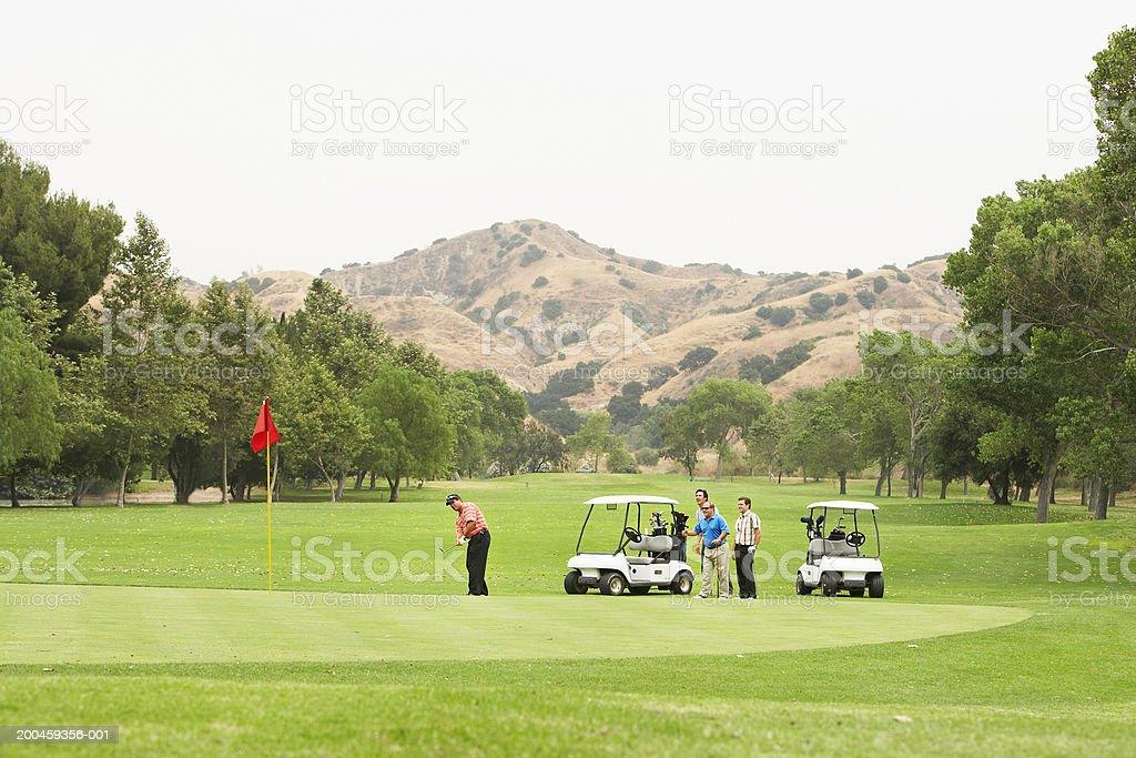Men playing golf, carts on green royalty-free stock photo