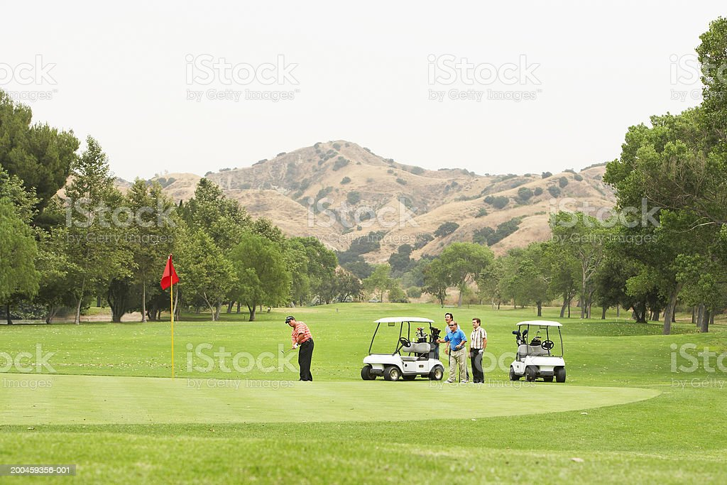 Men playing golf, carts on green stock photo