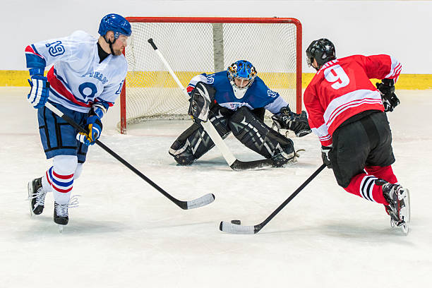men playing ice hockey - hockey stock pictures, royalty-free photos & images