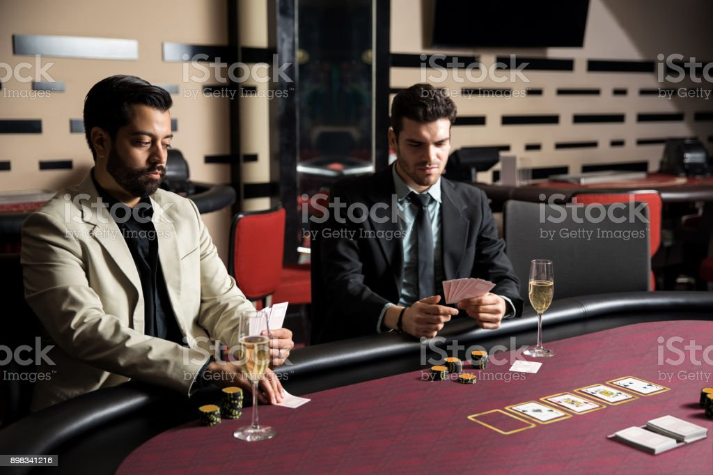 Men playing poker at a casino stock photo