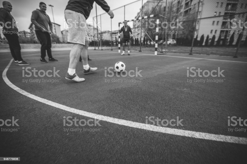 Men playing soccer outdoors stock photo