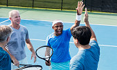 A multi-ethnic group of four mature and senior men playing tennis outdoors. They are standing together at the net, smiling. The African-American player, a senior man in his 70s, is giving a high-five to one of his opponents.
