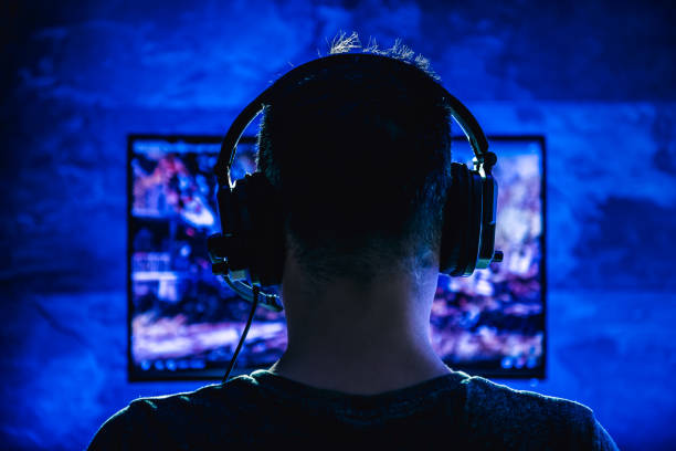 Men playing video games Men wearing headphones playing video games late at night computer games stock pictures, royalty-free photos & images