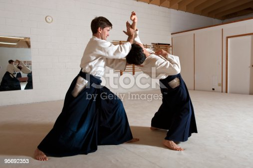 men wearing hakamas, practicing techniques in the dojo