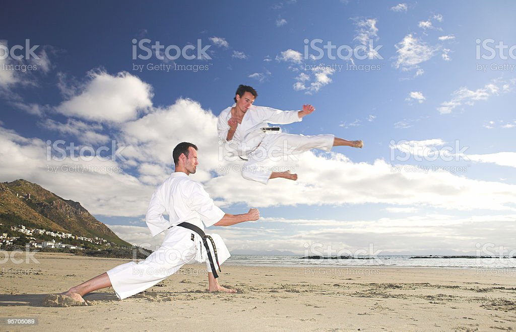 Men practicing Karate on the beach stock photo