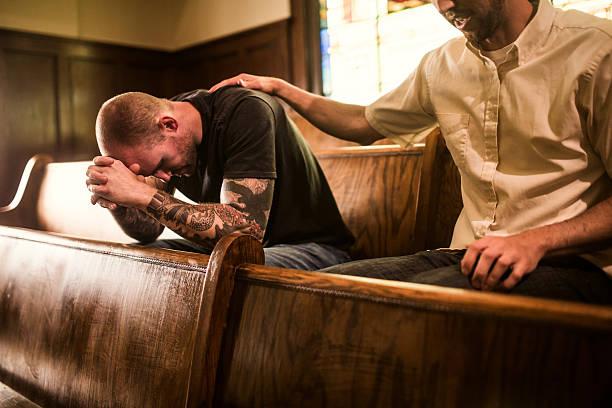 männer beten in der kirche - freundin tattoos stock-fotos und bilder