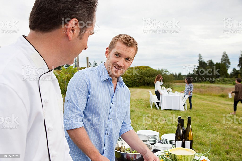 Men preparing meal in a field stock photo