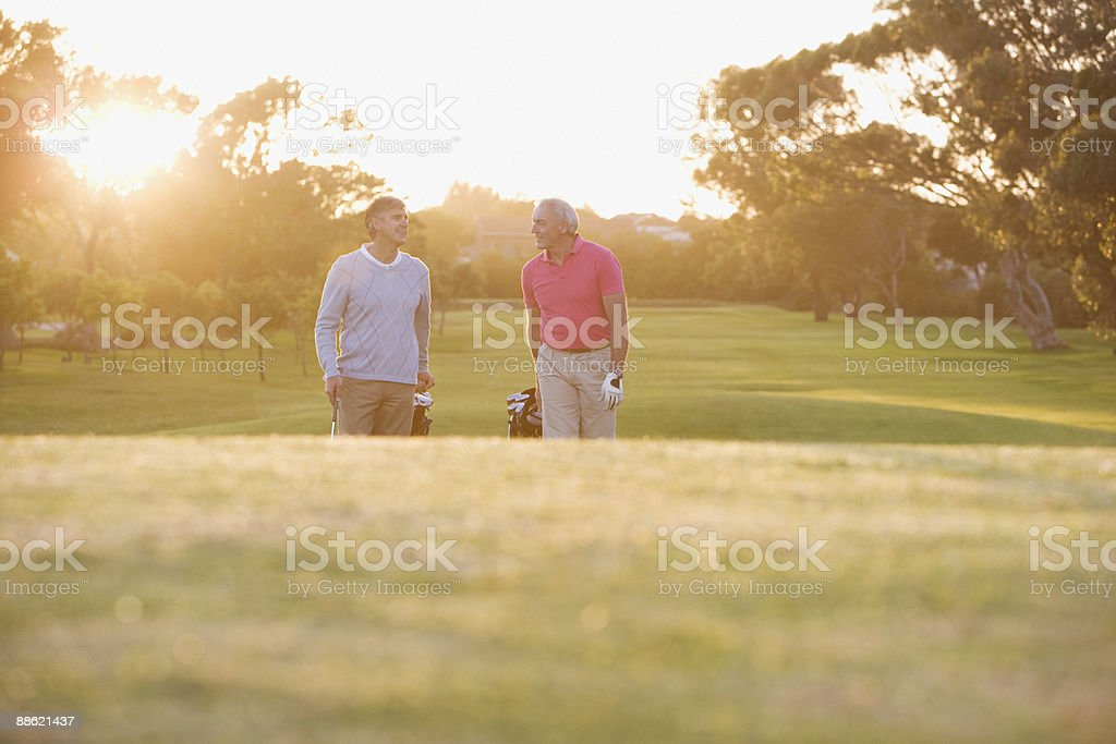 Men pulling golf carts on golf course royalty-free stock photo