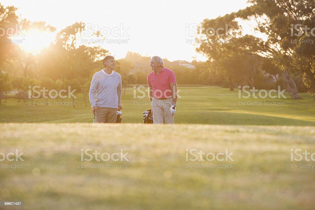 Männer ziehen Golfwagen auf den Golfplatz Lizenzfreies stock-foto