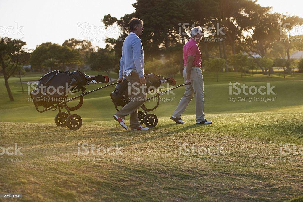 Homme tirant des voiturettes de golf sur le parcours de golf photo libre de droits