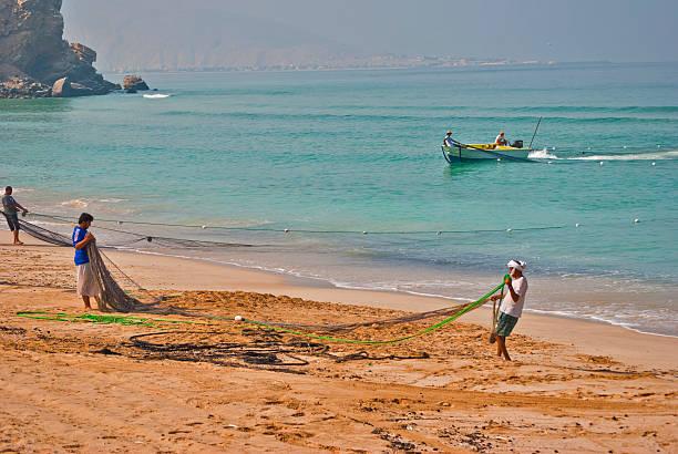 Men pulling in fishing net, Khasab, Oman stock photo