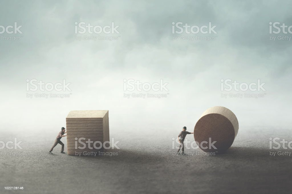 men pushing different geometric wooden shapes - Стоковые фото Абстрактный роялти-фри
