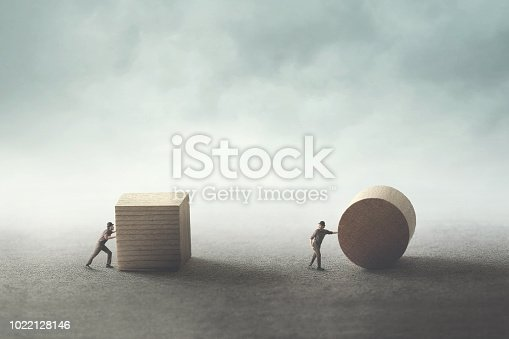 istock men pushing different geometric wooden shapes 1022128146