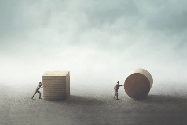 men pushing different geometric wooden shapes stock photo