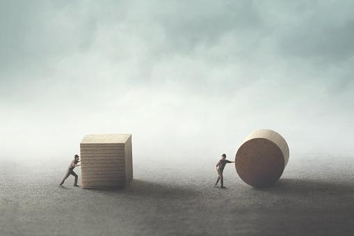 Men Pushing Different Geometric Wooden Shapes — стоковые фотографии и другие картинки Абстрактный