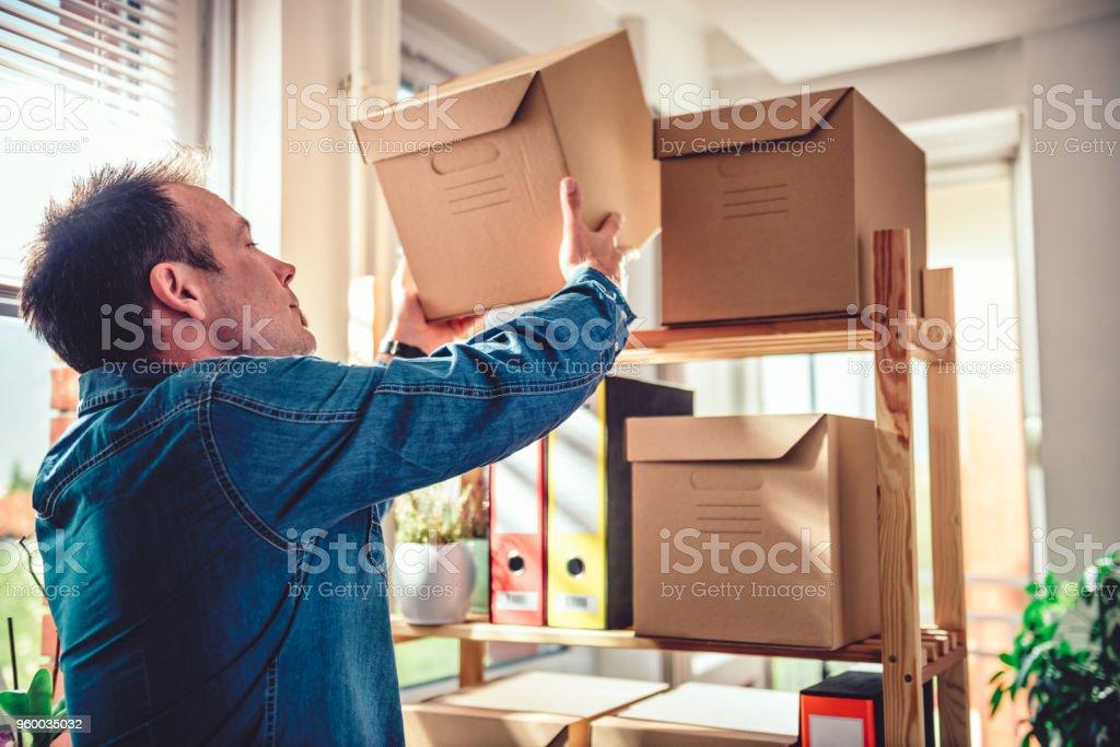 Men putting back box on the shelve stock photo