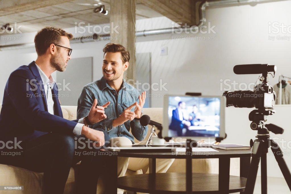 Männer, die ein Geschäft Vlog auf Kamera aufnehmen Lizenzfreies stock-foto